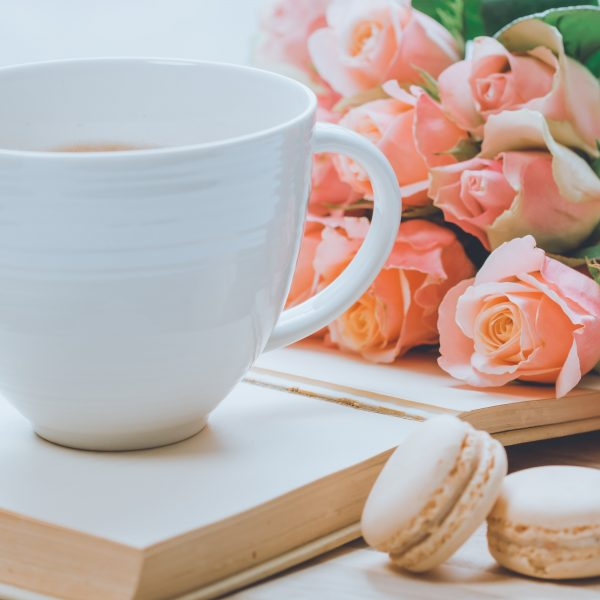 close-up-photo-of-coffee-mug-near-pink-roses-and-macarons-2014694