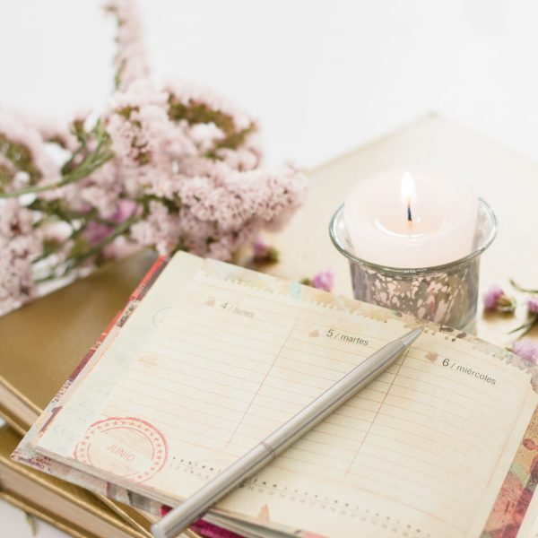 pretty journal with pink flowers, pen and candle
